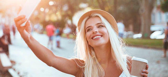 chica rubia con sombrero haciéndose un selfie