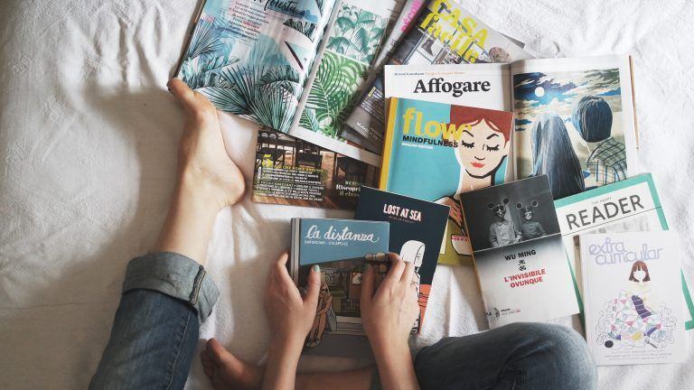 persona sentada en la cama con libros
